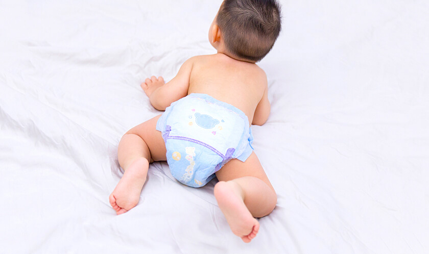 infant crawling on bed